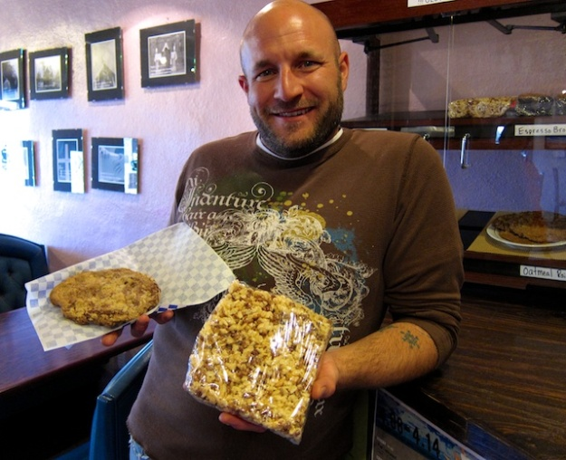 Lela holds up monstrous Rice Krispies squares and cookies at The Coffee Spot