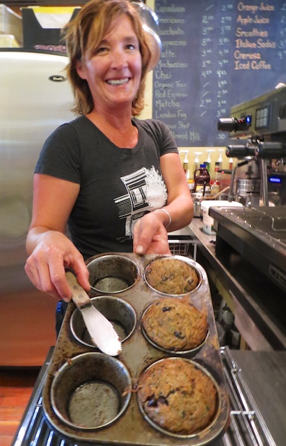 Owner Niki Dusseault  lifts unbelievable chocolate zucchini muffins at Bacchus Books & Cafe