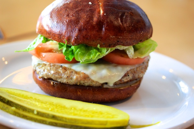 A whiskey-garlic pork burger on a pretzel bun. Yum!